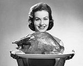 Woman holding platter with roast turkey