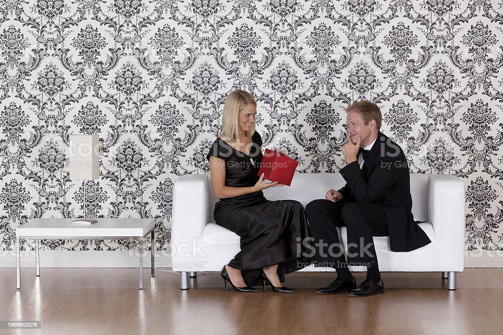 Woman holding present and sitting with a man on couch stock photo