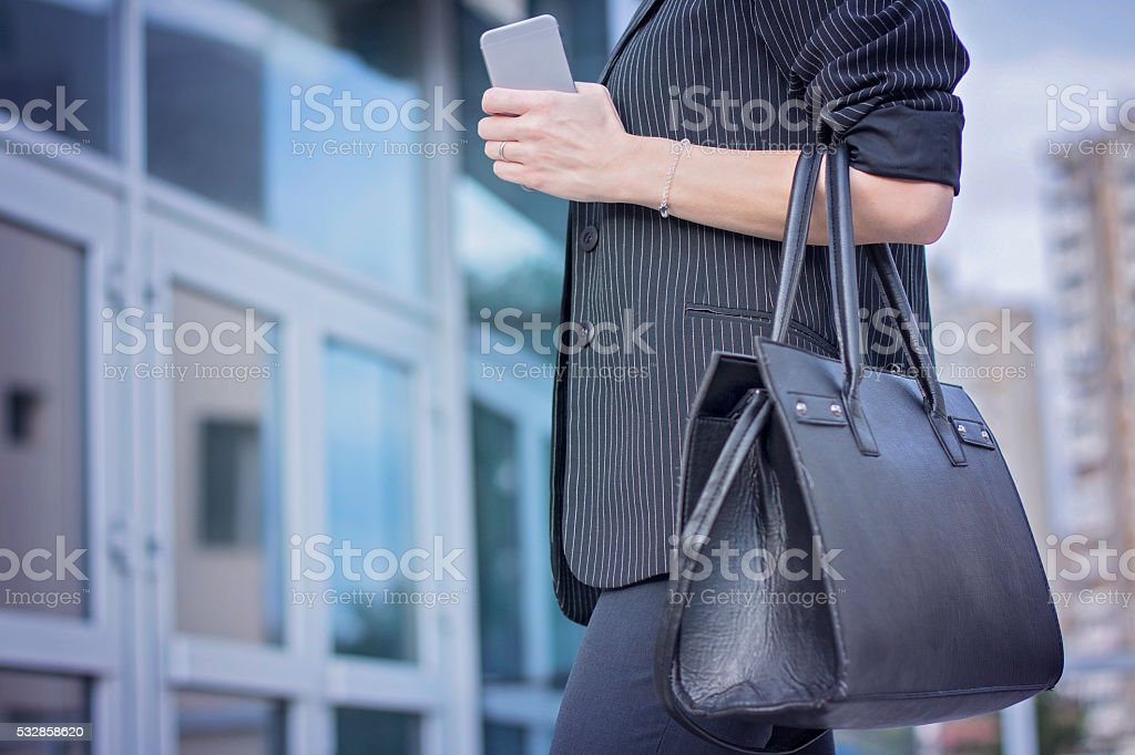Woman holding purse and phone in front her office stock photo