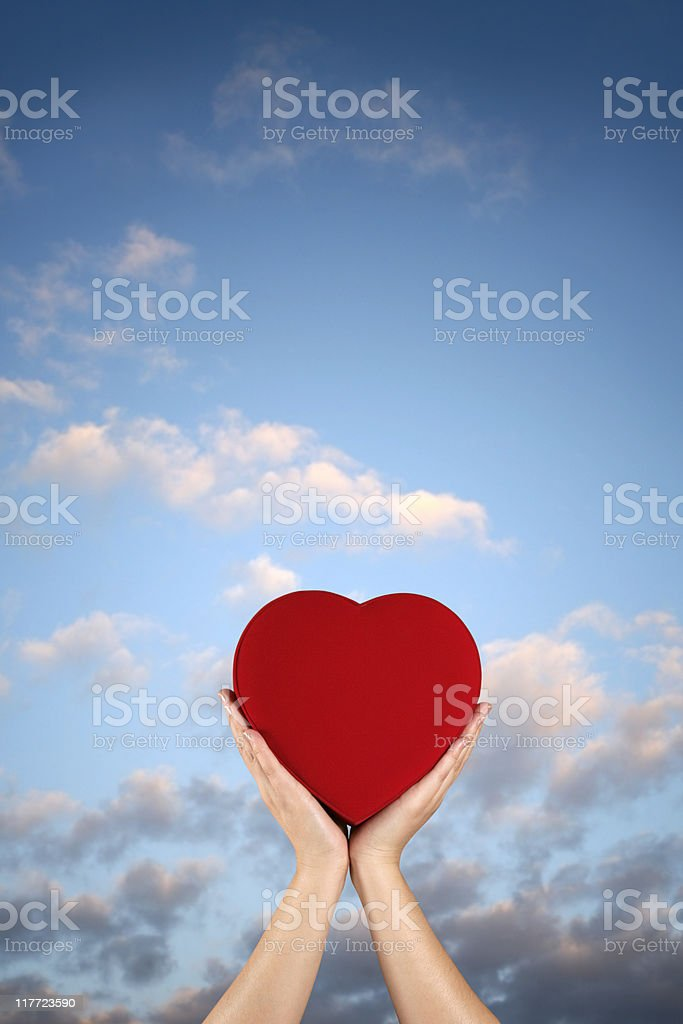 woman holding red heart over sky royalty-free stock photo