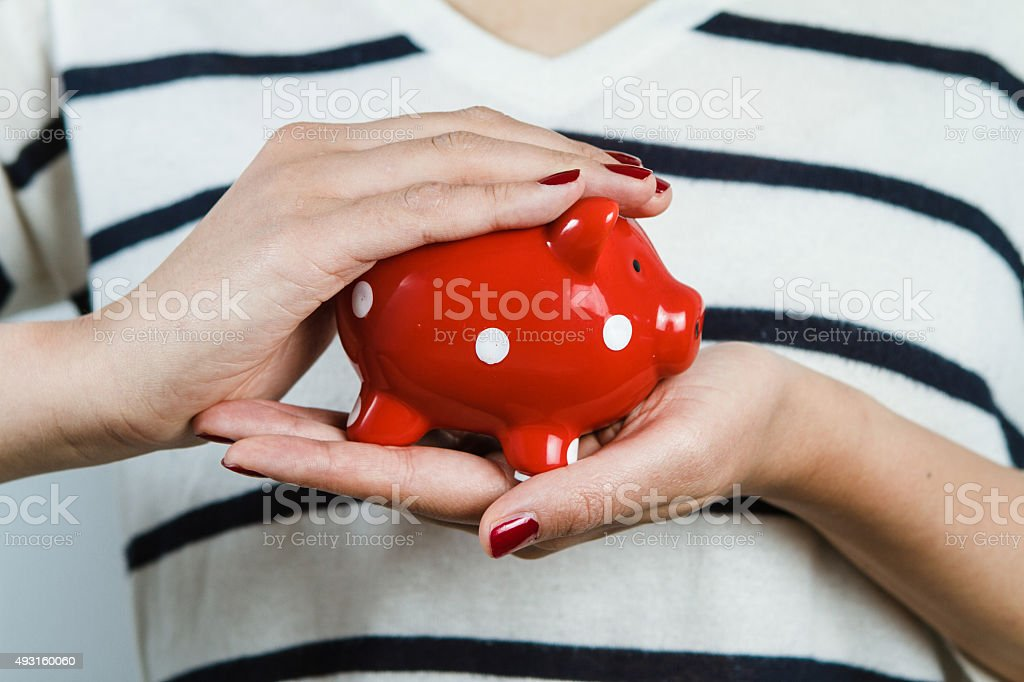 Woman holding red piggy bank stock photo