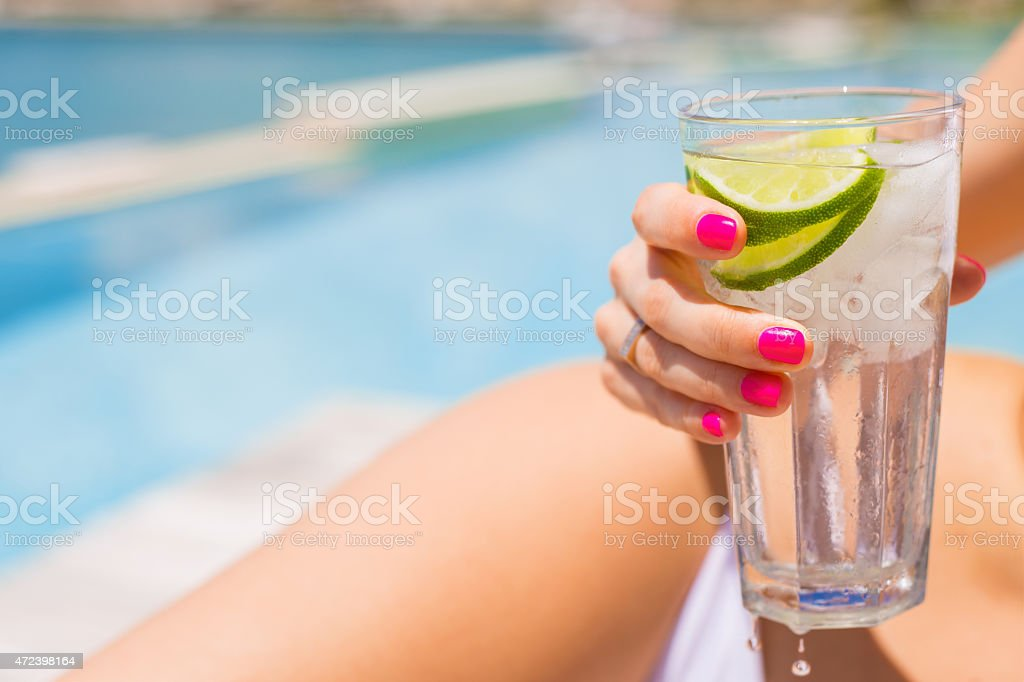 Woman holding refreshing cold drink by the pool stock photo