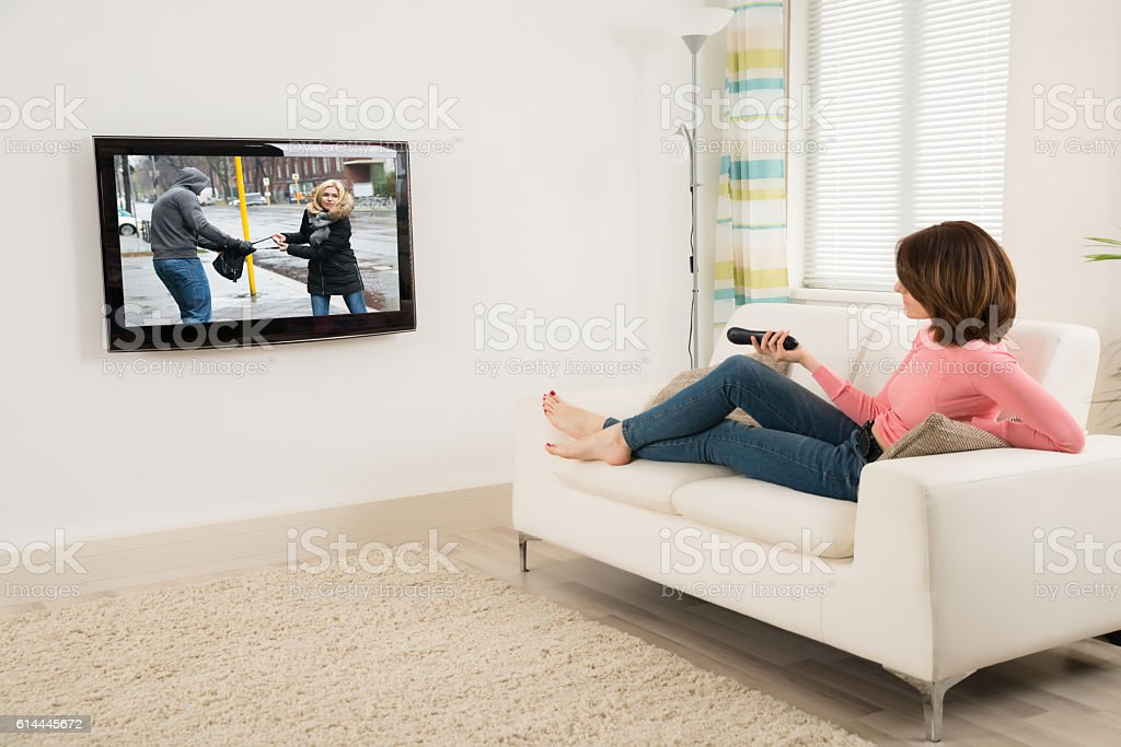 Woman Holding Remote While Watching Television stock photo