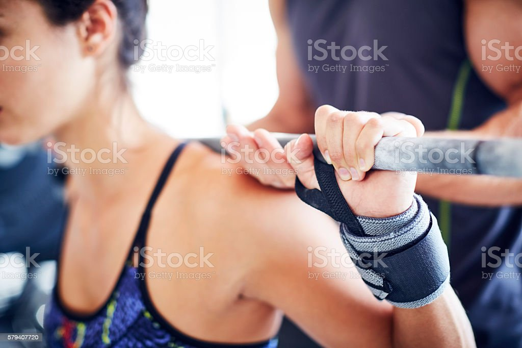 Woman holding rod of barbell while instructor assisting her stock photo