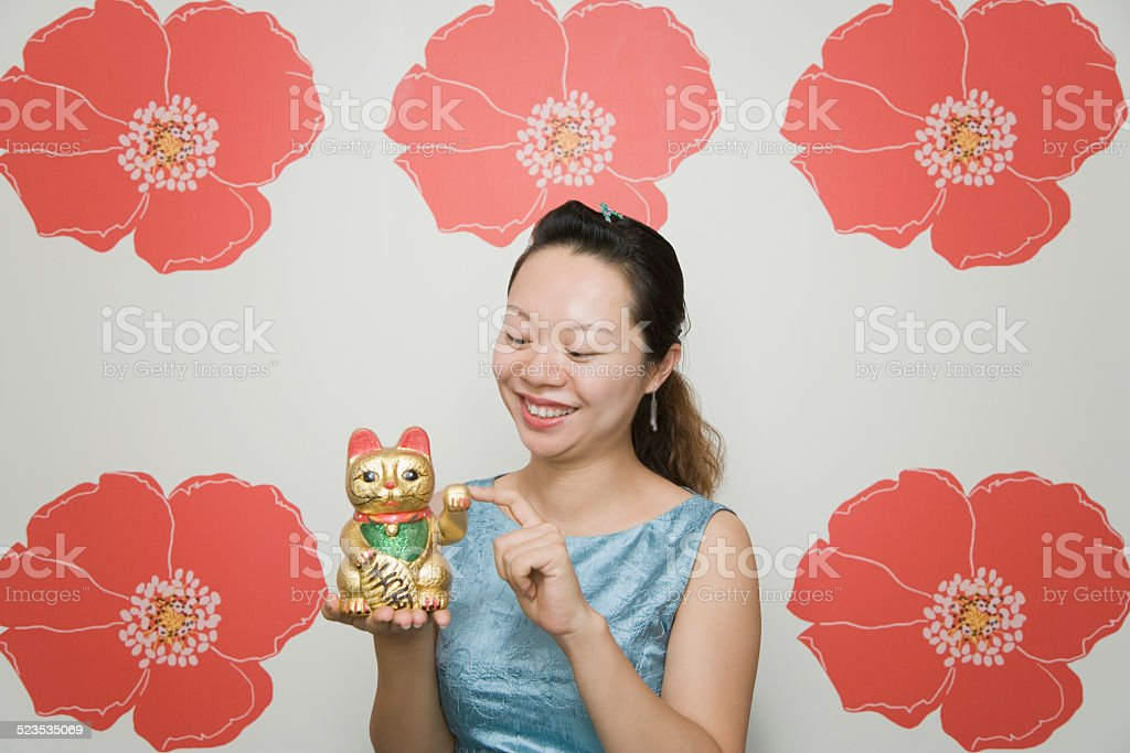 Woman holding sculpture of traditional fortune cat Maneki Neko stock photo