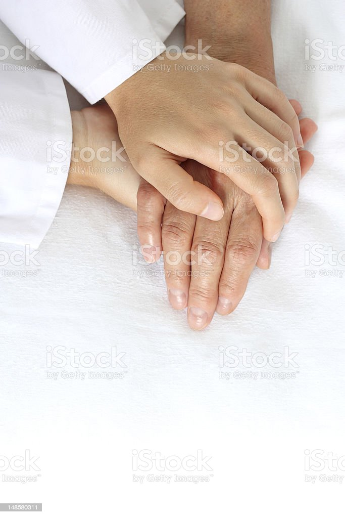 Woman holding senior hand on bed royalty-free stock photo