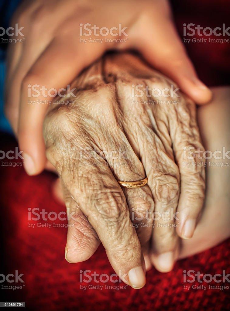 Woman holding senior woman's hand stock photo