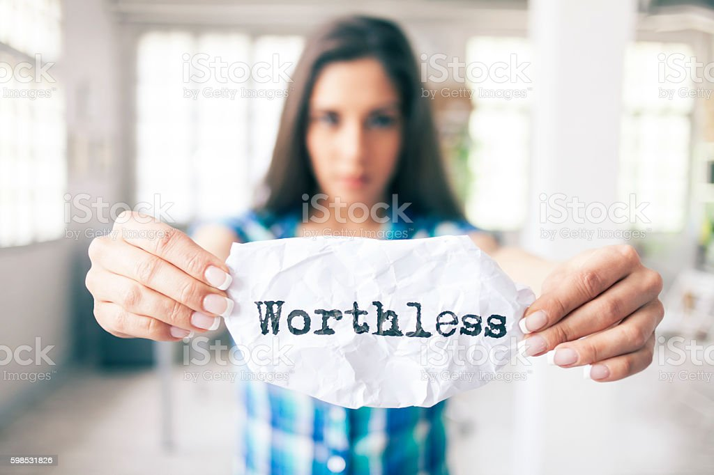 Woman holding sheet of paper with message 'worthless' stock photo