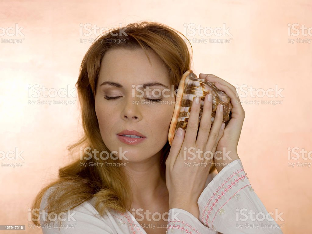 Woman holding shell on ear, eyes closed stock photo
