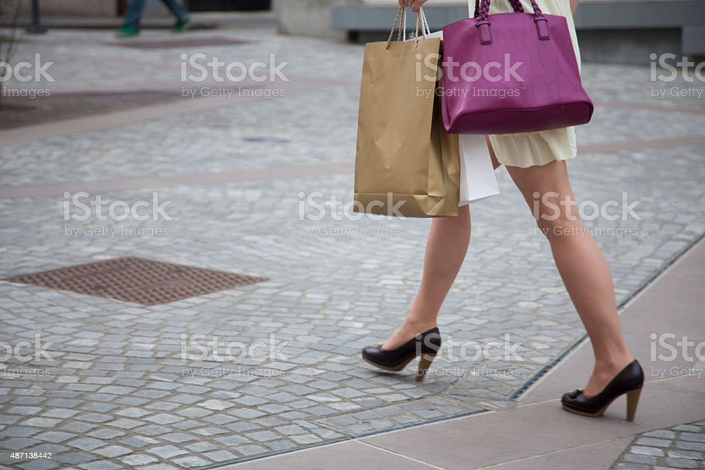 Woman holding shopping bags and walking stock photo