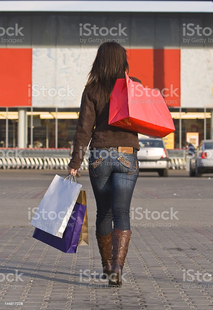 Woman holding shopping bags walking into a supermarket royalty-free stock photo