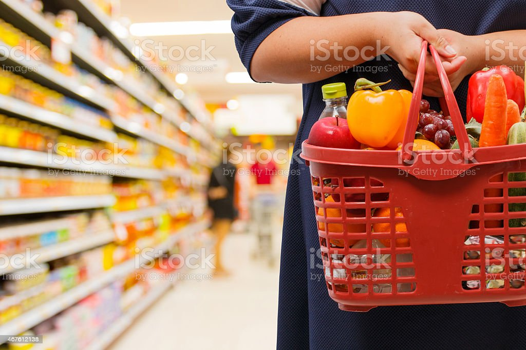 woman holding shopping basket in supermarket stock photo