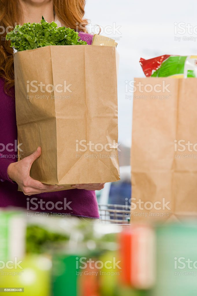 Woman holding shopping paper bag in supermarket stock photo