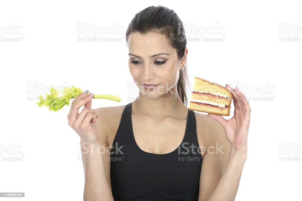 Woman Holding Slice of Cake and Celery Stick stock photo