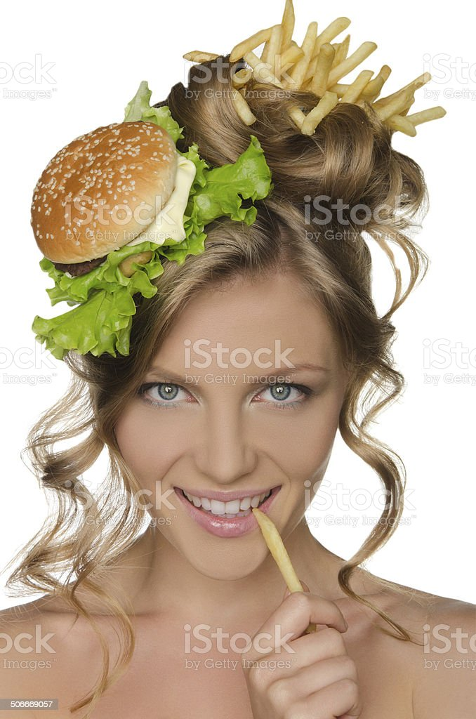 Woman holding slice of potato at mouth stock photo