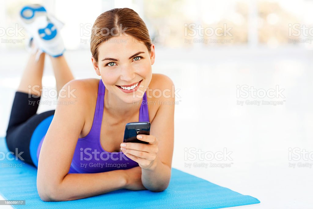 Woman Holding Smart Phone While Lying On Exercise Mat royalty-free stock photo