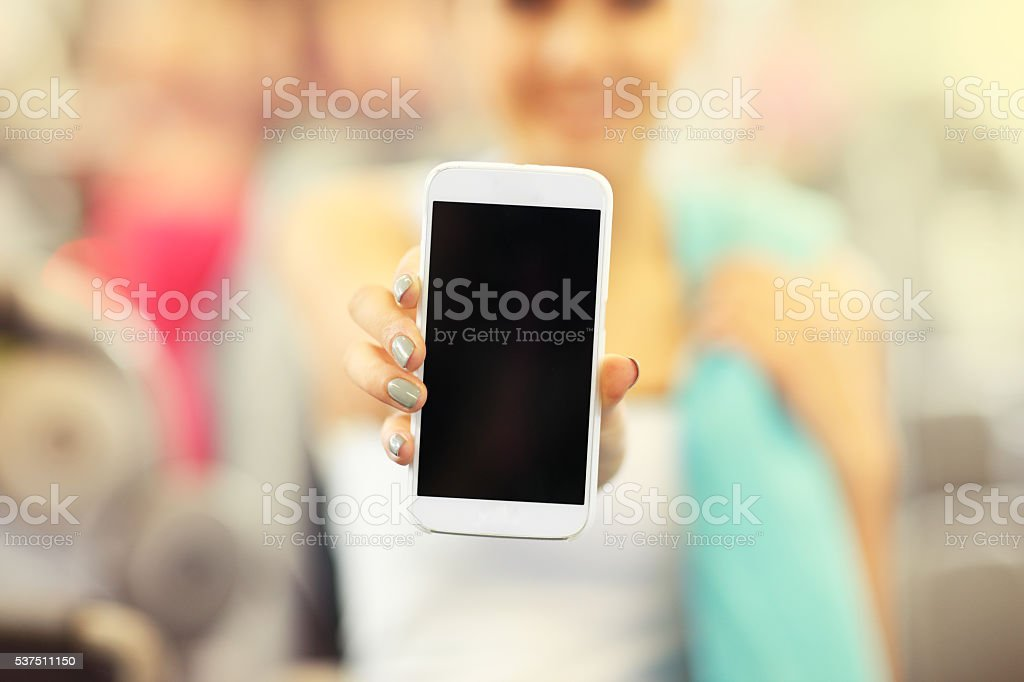 Woman holding smartphone in gym stock photo