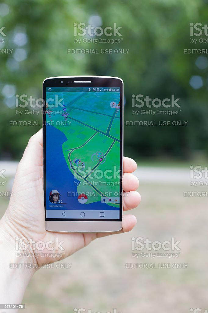 Woman Holding Smartphone playing Pokemon Go stock photo