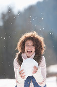 Woman holding snowball, smiling