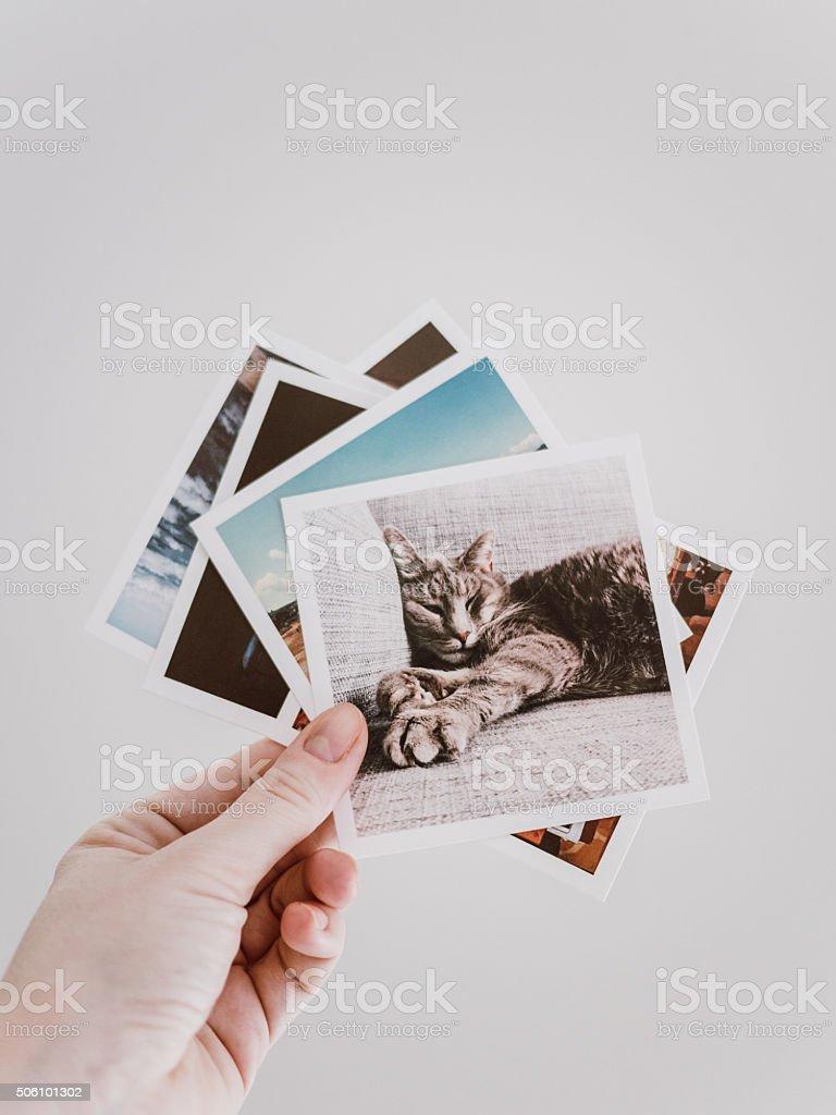 Woman holding social media photo prints stock photo