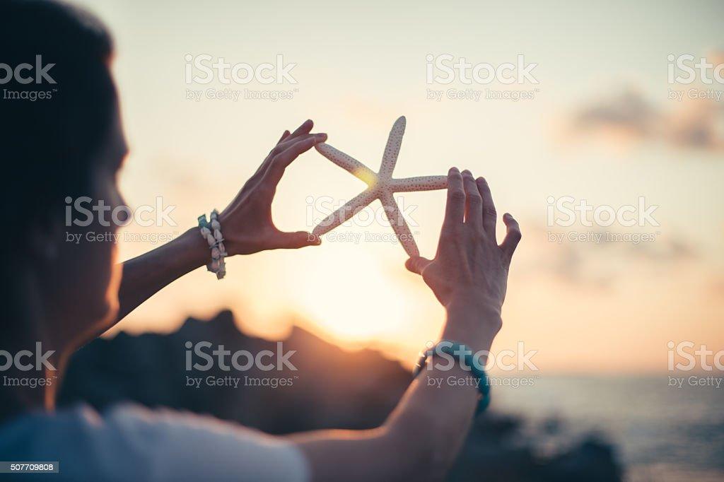 Woman holding starfish on sunset stock photo