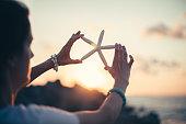 Woman holding starfish on sunset