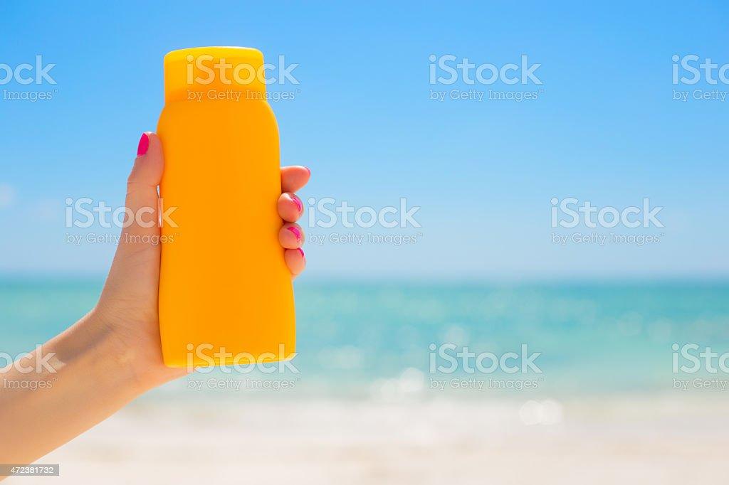 Woman holding sunscreen bottle stock photo