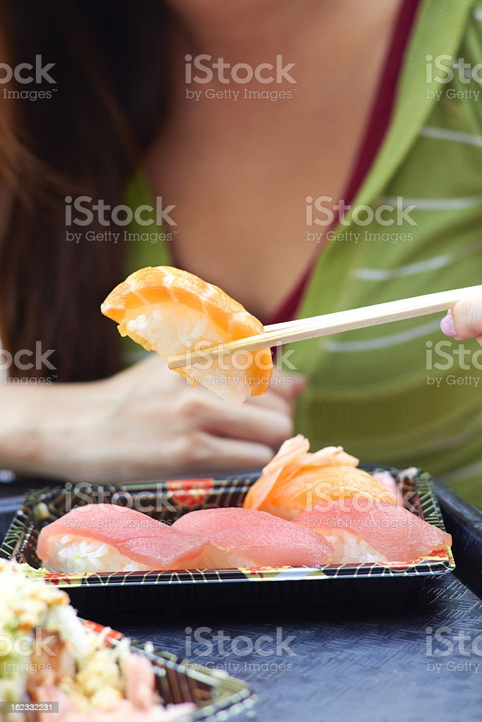 Woman Holding Sushi With Chopsticks royalty-free stock photo