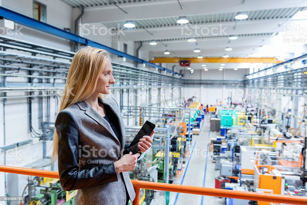 Woman holding tablet on top of a new factory stock photo