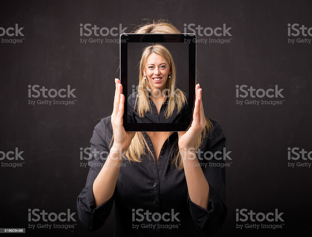 Woman holding tablet with her happy face stock photo