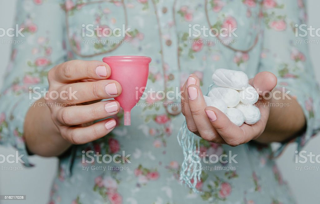 Woman holding tampons and menstrual cup in hands stock photo