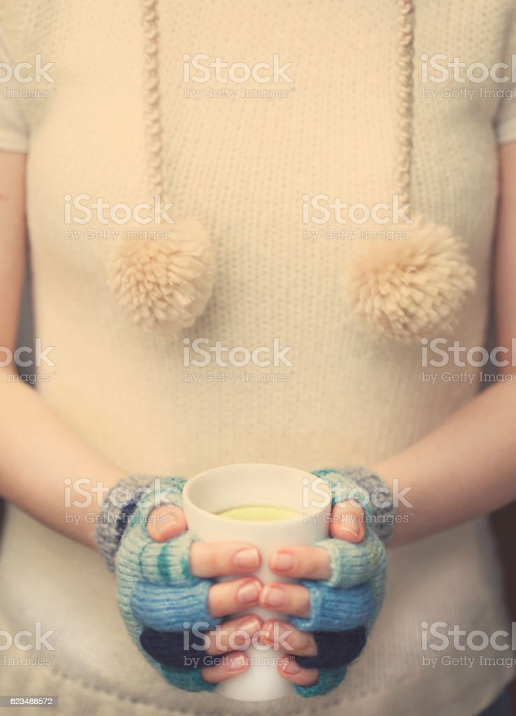 Woman holding tea cup with two hands stock photo