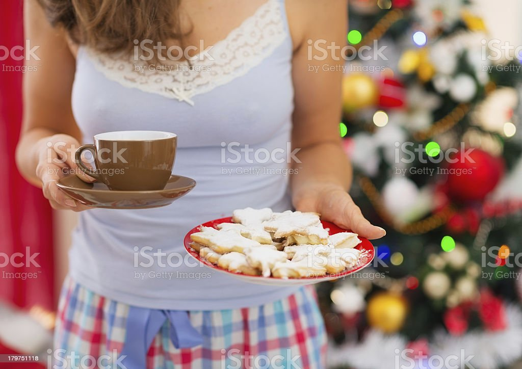 Woman holding tea in front of Christmas tree. Closeup royalty-free stock photo