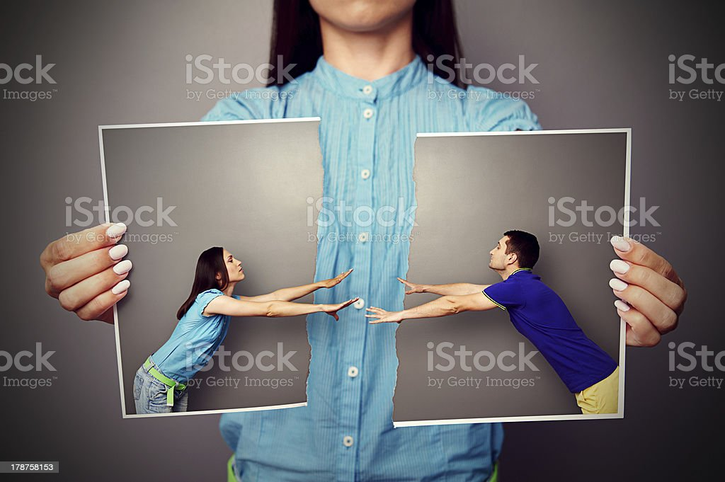 woman holding the lacerated photo of couple stock photo