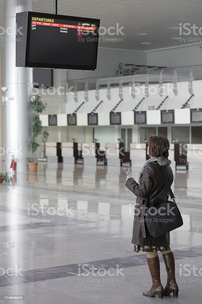 Woman holding ticket and looking at departures screen in airport royalty-free stock photo