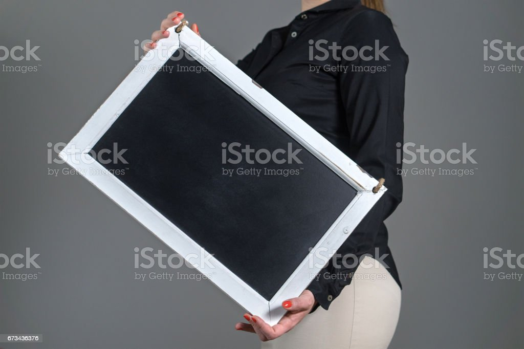 Woman holding tilted chalkboard on a dark gray background. Free blank empty copy space for text, menu or specials. Waitress in a restaurant or business person. stock photo