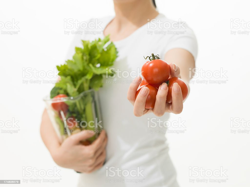 Woman holding tomatos and Vegetable juicer stock photo