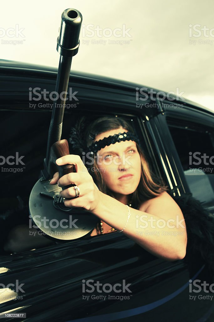 Woman Holding Tommy Gun Outside of Car royalty-free stock photo