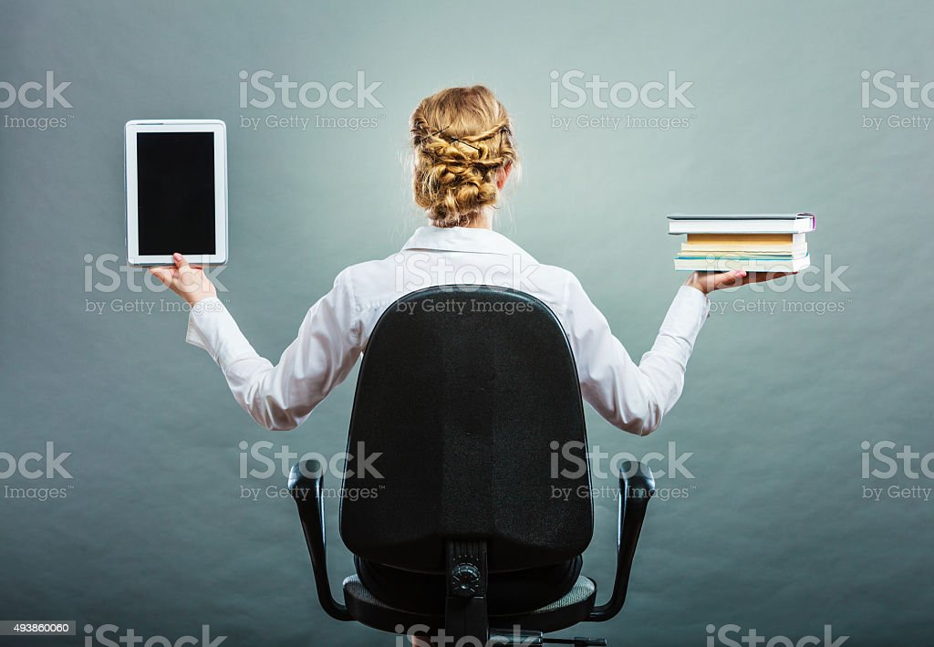 Woman holding traditional book and e-book reader stock photo