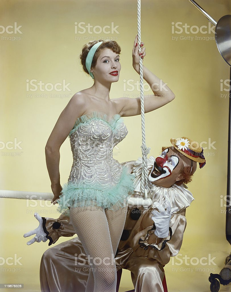 Woman holding trapeze bar with clown, smiling stock photo