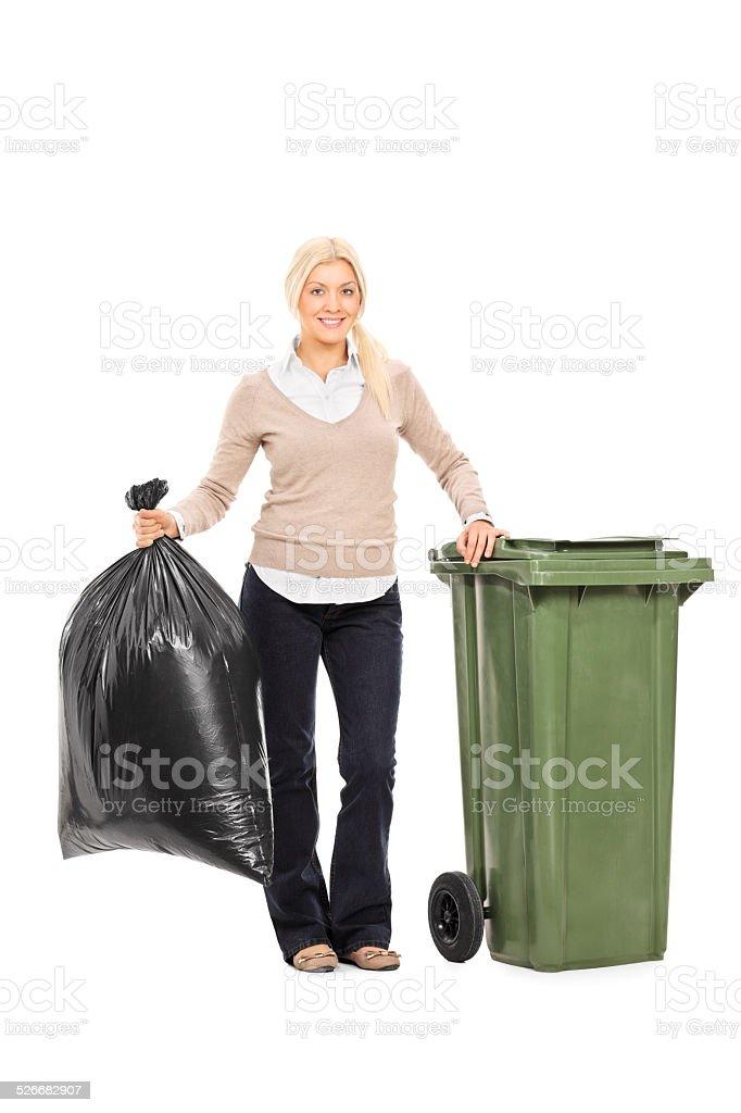 Woman holding trash bag next to a garbage bin stock photo