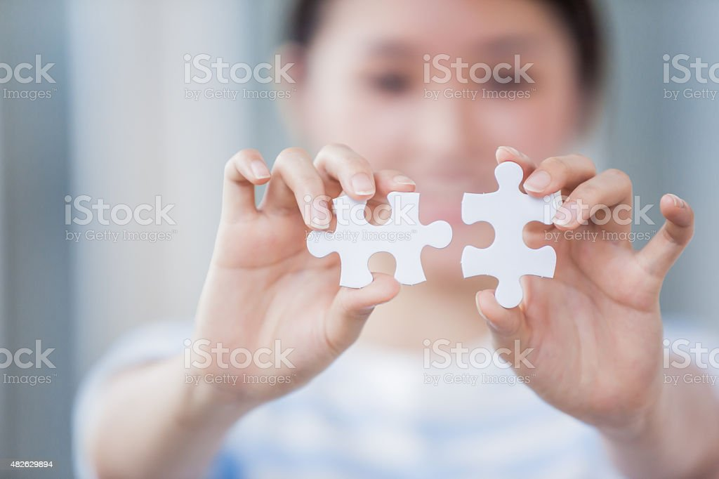 Woman Holding Two Pieces of Puzzles Together stock photo