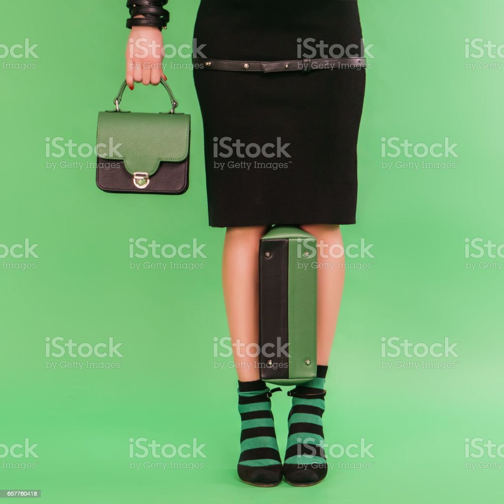 Woman holding two woman's handbags on a green background stock photo