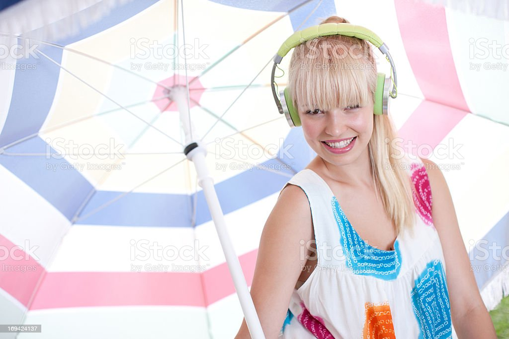 Woman holding umbrella listening to headphones stock photo