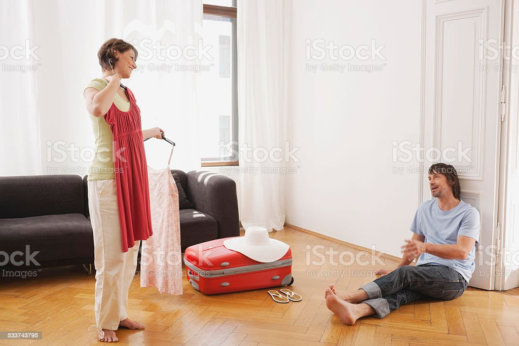 Woman holding up dress man leaning against door stock photo