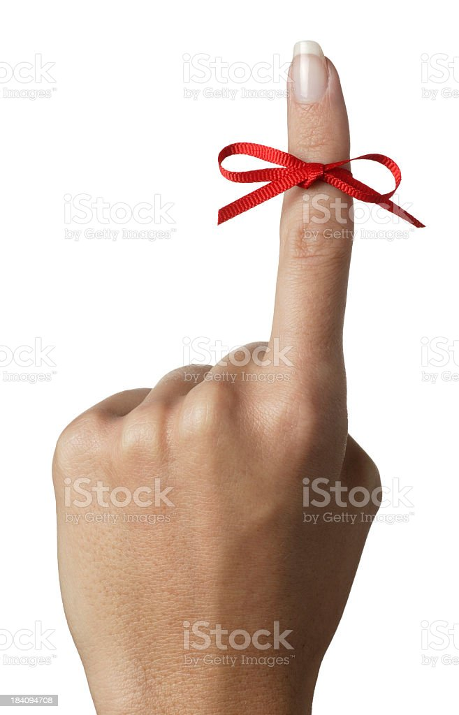 Woman holding up index finger tied with red bow stock photo