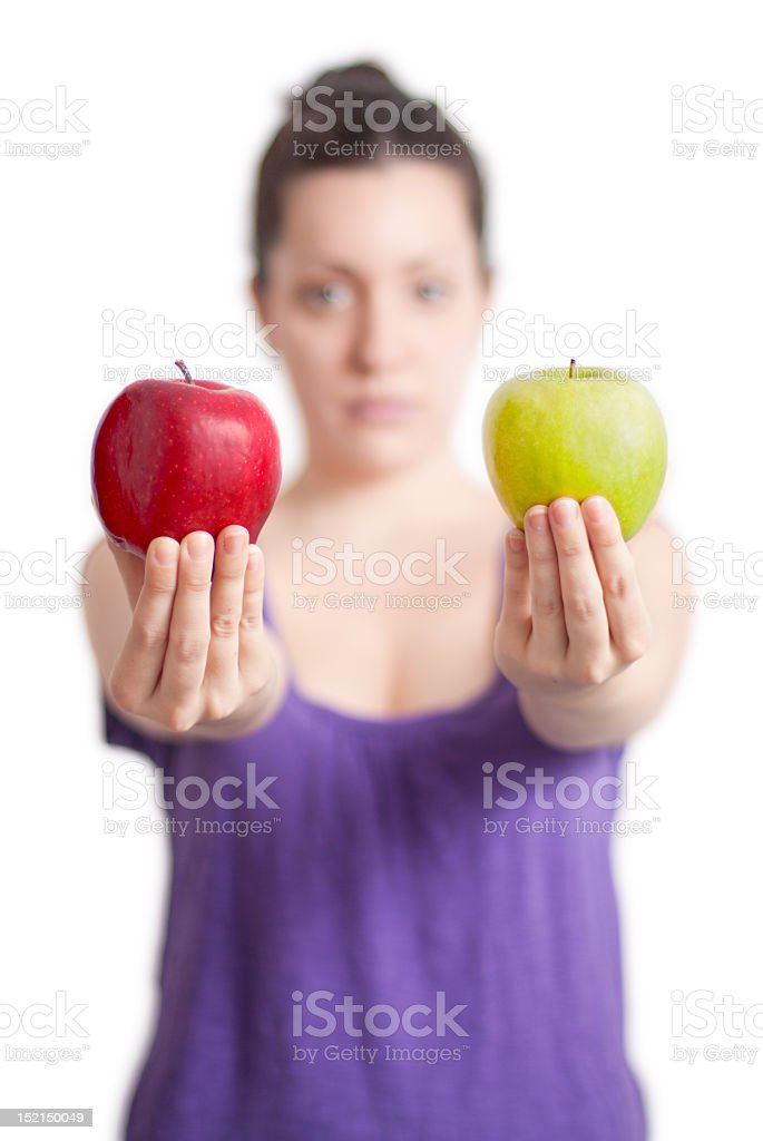 Woman holding up one red apple and one green apple royalty-free stock photo