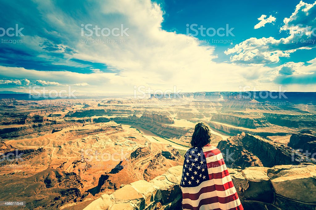 Woman Holding US Flag at Grand Canyon Landscape, USA stock photo