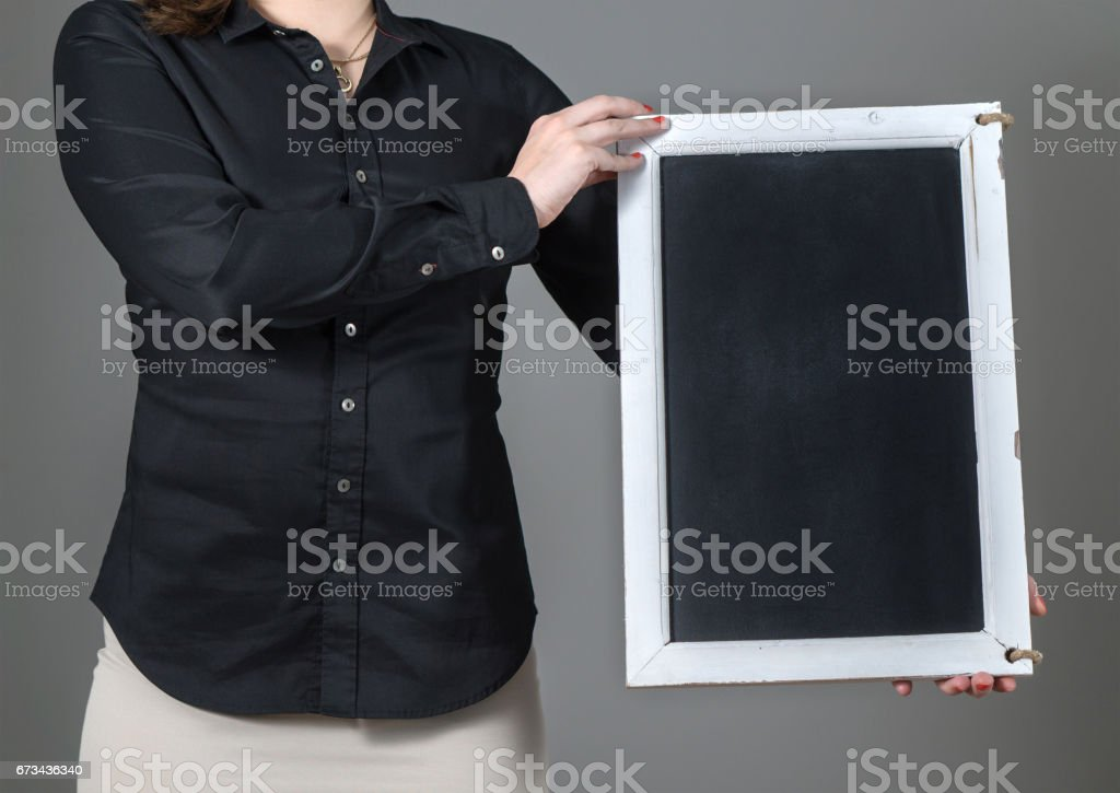Woman holding vertical chalkboard on a dark gray background. Free blank empty copy space for text, menu or specials. Waitress in a restaurant or business person. stock photo