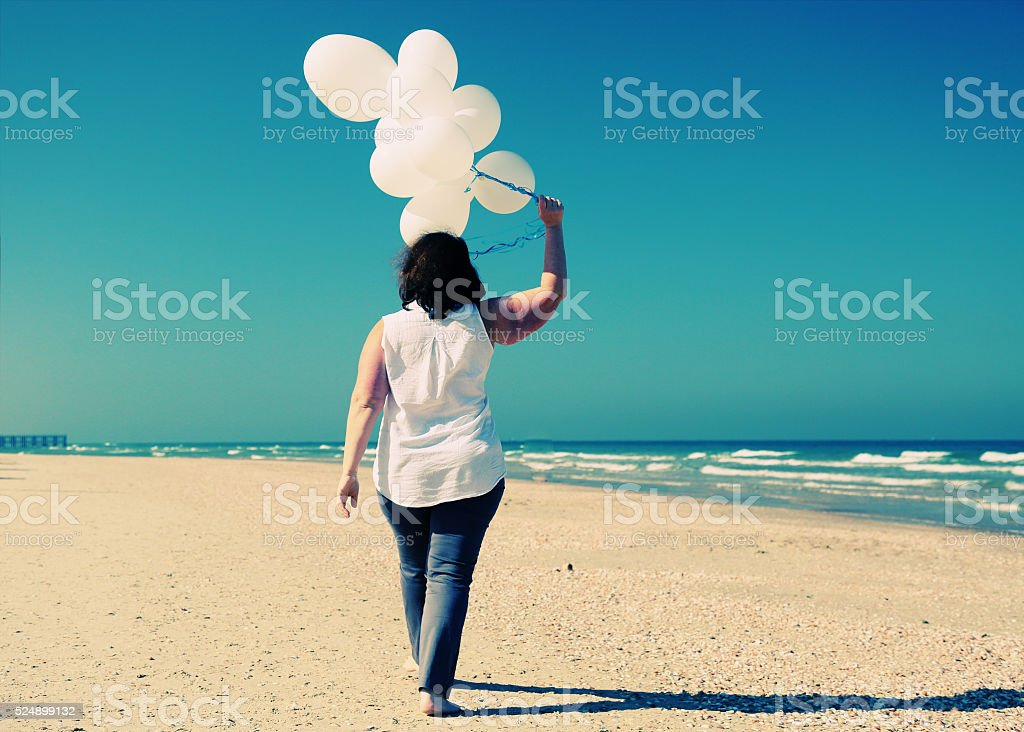 woman holding white balloons stock photo